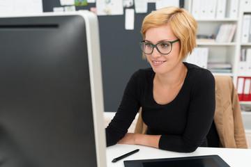 moderne junge frau schaut auf pc-monitor