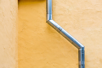 Drainpipe against yellow wall