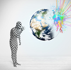 Funny man in body suit looking at colorful splatter earth