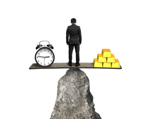 man standing between clock and gold balancing on rock seesaw