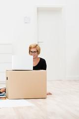 junge frau im büro mit laptop und karton