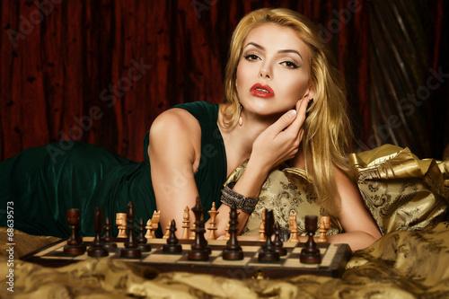 Blond woman playing chess - 68639573
