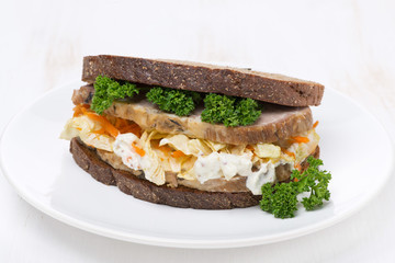 sandwich with coleslaw and baked meat on the plate