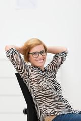 frau im büro lehnt sich lächelnd zurück