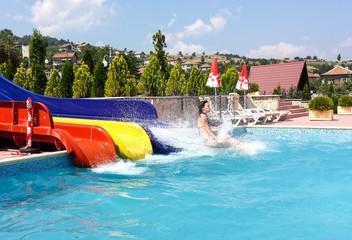 Frau rutscht in einen Pool, mit blauem Himmel und Sonnenschein