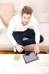 Junger Mann mit Tablet Pc auf dem Sofa