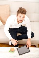 Junger Mann mit Tablett Pc auf dem Sofa