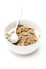 Bowl and spoon with corn flakes on the white background