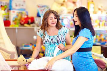 pregnant women choosing goods for baby