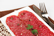 Tasty salami on plate on  napkin isolated on white