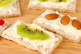 Tasty canapes with cheese, kiwi and cranberry, almond,
