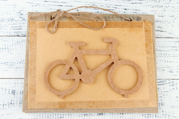 Decorative bicycle on book on wooden background