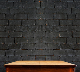 Black brick wall and wooden table,perspective background