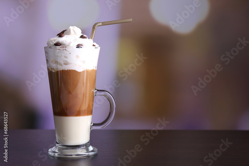 Fotobehang Cafe Glass of coffee on color wooden table, on dark background