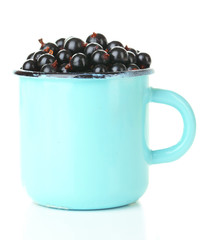 Ripe blackcurrants in mug isolated on white.