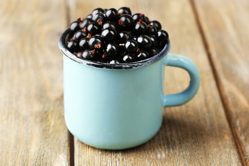 Ripe blackcurrants in mug on wooden background.