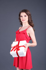 Beautiful young girl in red dress with on grey background