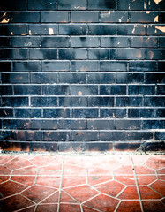 grunge black brick wall and stone pavement floor