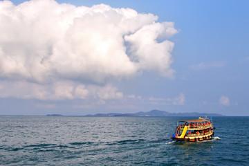 лодка с туристами плывет на фоне моря и облака