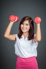 Healthy Asian girl hold  dumbbells and smile