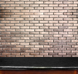 Empty black marble table and white brick wall in background. pro