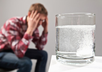 Stressed man sitting with head ache migraine near glass of water