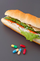 Pills and two hot dogs with various ingredients