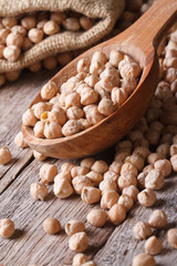 Raw chickpeas in a wooden spoon close-up  vertical