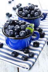 Delicious blueberries in cups on table close-up