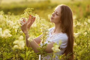 Happy girl among the high wildflowers