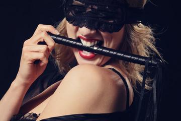femme sexy avec masque en dentelles et fouet