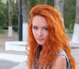 Head and shoulders image of a young women with red hair outdoors