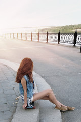 Red haired girl sitting near her scateboard