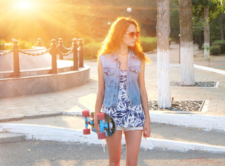 Beautiful young woman standing with skateboard in her hands