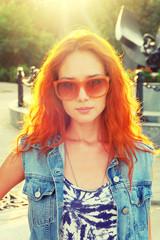 Street fashion women in orange sunglasses backlit.