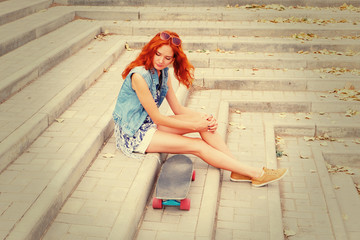 Redhead women sitting on street stairs hear her skate board