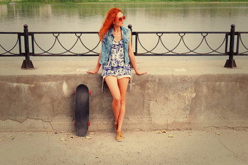 Beautiful woman posing with a skateboard