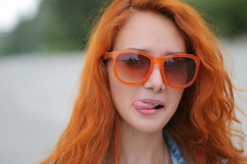 Young red haired women posing in orange sunglasses