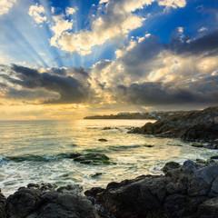 sea wave breaks about boulders at sunrise © Pellinni