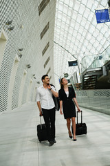 young business travelers walking in public station