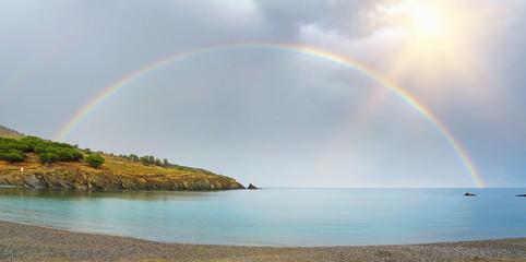 Panorama of a rainbow half over sea and land