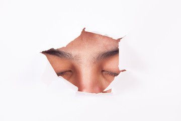 closed eyes through paper hole