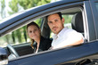 cheerful young business couple in car