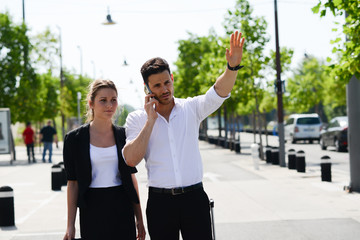 young business couple waving a taxi cab in public station