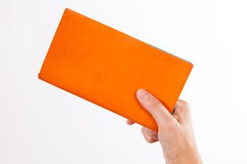 Hands showing or offering blank orange book