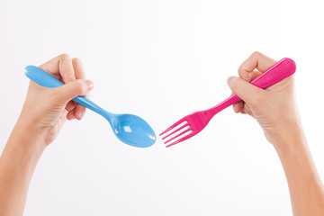Female Hand Holding colorful fork and spoon