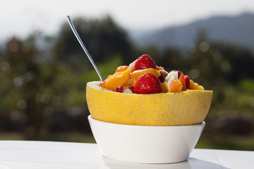Fruit salad served in a bowl of melon