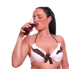 Frau im Bikini schwitzt und trinkt aus einem Glas