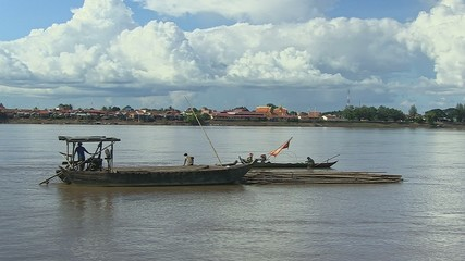 A bamboo raft is  towed a bamboo by a small boat