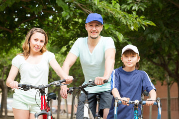 Positive tourists with son riding bicycles in park